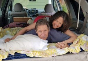 Camp for Free author and former Mount Shasta resident John Soares on the platform bed in his minivan with his sweetheart Stephanie Hoffman